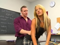 A blonde is getting kissed and rammed on the desk in detention