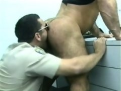 Prison guard does a cavity search on a burly inmate with his tongue and cock