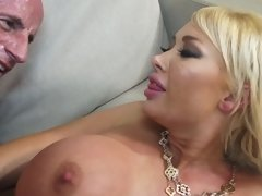 A blonde with large tits is fucked in her wet cunt on the sofa